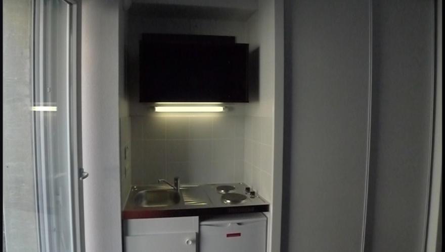 Appart.T1: Cuisine, étagère et placards.